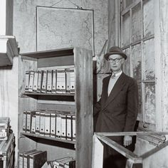 """Johannes Kleiman next to the bookcase after the war. In her book """"Memories of Anne Frank"""" Miep Gies writes that during the war Johannes Kleiman had horrible stomach pains. Miep think this happened because he was extremely concerned about the people in hiding."""