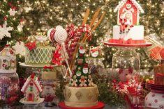 mesa de doces decorada para natal com bolos temáticos de árvore de natal, casinha do papai noel e espírito santo.