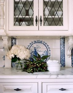 white kitchen with marble counter and spiraling drawer handles and blue painted tile