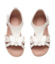 Sandalen aus Lacklederimitat mit schimmerndem Schmetterling vorn und verstellbarem Klettriegel an der Seite. Futter aus Velourslederimitat und Innensohle aus Lederimitat. Gummisohle.