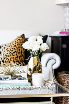 Well-styled coffee table with a gold vase and white roses