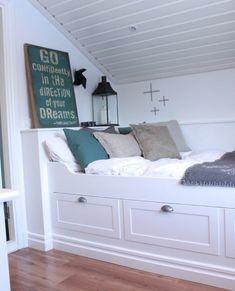 chambre sous combles minuscule, lit blanc avec rangements, linge de lit blanc, coussins gris et vert, parquet clair, peinture mur blanc, chhambre mansardée