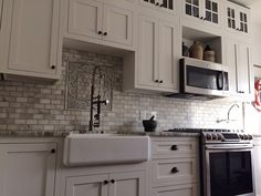 White kitchen with Brown Fantasy Leathered quartzite countertops, a white farm sink, & gorgeous Calacatta Oliva backsplash tile.  Kitchen by Stoneshop from Cherry Hill, NJ.