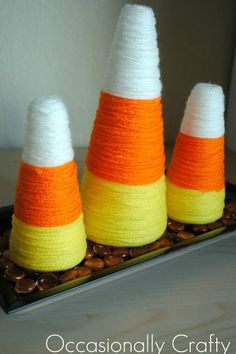 Craft your favorite Halloween candy by spiraling yellow, orange, and white yarn around Styrofoam cones dotted with hot glue. They look so good, we could (almost) eat them.