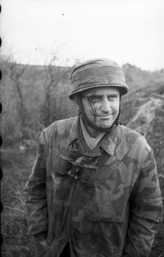 A lightly wounded German Fallschirmjäger (paratrooper) grins for the camera during the Battle of Monte Cassino of the Italian Campaign. Near Cassino, Frosinone, Lazio, Italy. ca. March 1943.