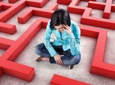 sofferenza: Triste ragazza si siede in un labirinto con pareti rosse