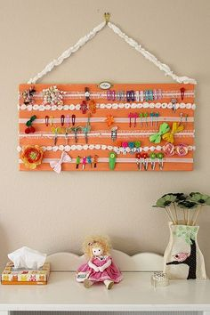 Paint a canvas, staple ribbon, place some brads on ribbon so doesn't sag, scre hooks and ribbon to hang add sign with scrapbook supplies and wah-lah! I'm so doing this for Makenna this summer.