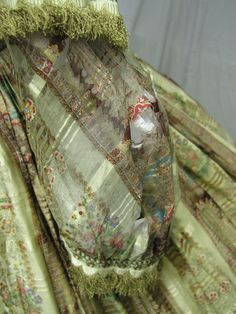 """1850s/1860s Silk Sheer Print Dress. The seller says: """"This lovely 1860's civil war era dress was created of fine silk blend sheer fabric in a gorgeous pattern.  The colors are still rich and lovely.  It is totally lined in a off white cotton which is in good vintage condition.  The bust is 31, the waist is 21, the skirt length is 43 and it is 164 inches around the bottom. I purchased this from the first Augusta auction that sold part of the Brooklyn Museum collection."""" Tears in sleeve."""