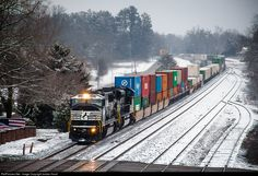 RailPictures.Net Photo: NS 6734 Norfolk Southern EMD SD60I at Lula, Georgia. Charlotte to Atlanta intermodal 221 eases through a snow covered downtown Lula as they approach a track crew at the new CP Lula. The former Conrail SD60I on the point is likely used to the snow, an otherwise rare event in the south. by Jordan Hood