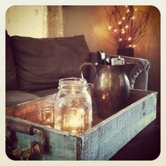 Rustic centerpiece for your coffee table! I found this rough wood box with rope handles at TJ Maxx and took three different sized mason jars from home and put tea lights in each one. We found an antique pitcher at a yard sale for our remotes. This gives our living room a warm comfy feel.