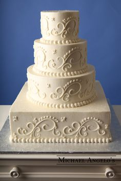 Large Ornate Swirls #17Classic This four-tier, ivory cake is a little different in that the bottom tier is square-shaped. It's classic and elegant look is due to the large ornate swirls made of buttercream.