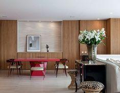 A área social do apartamento paulistano gira em torno de um forno de pizza oculto por painel de madeira, em meio a mobiliário assinado e obras de arte. Projeto Deborah Roig.
