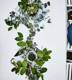An aerial view of a set table with a white tablecloth and a table runner centrepiece made from mirrors, greenery and small succulents