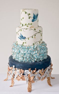 Ornate wedding cake with silver leaf and hand painted birds