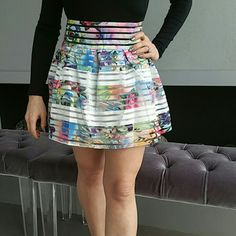 """Floral skirt NWT BRAND NEW WITH TAG  Gorgeous floral print with white stripes skirt. Rows of floral elastic, white elastic and clear fabric make this skirt a true statement maker.  White lining Total length approx 15.5"""" zip up in back  Material 80% polyester 20% elastic Size large (juniors/petite large) (Pic #4 waist approx measurements, top pic in collage is when the skirt is stretched out, lower pic of collage is when the skirt is laid flat and not stretched.)  (Model is a size petite…"""