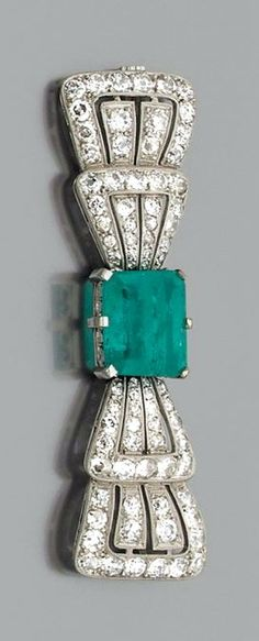 A diamond and platinum Art Déco brooch set with a rectangular-shaped emerald weighing approximately 5 cts. 1920's