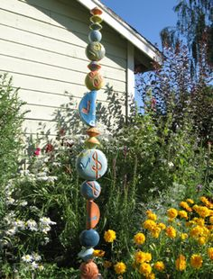 Garden Totem: I like this idea. How about threading a thin metal rod thru painted wooden wheels, knobs, beads, finials and those little birdhouses they sell at hobby or hardware stores?