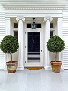 I love topiaries at the front door. A black door is also classic looking. Like the entrance is wearing a tuxedo.