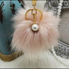 Light Brown Pom pom keychain with pearl NWOT! Brand new!! Faux fox fur but really soft and great quality. Gold hardware.  Size: (approx) Ball Diameter = 8cm  Its a keychain, you can also use it to put as purse charm or just to hold any key.  Great gift for your family, friends or your self.  ** color might be slightly different cause of the lightning  Great for your Louis Vuitton, Prada, Fendi, Chanel, Michael Kors, Gucci, Coach Tory Burch, Kate spade, Marc jacobs and others purses/bags…