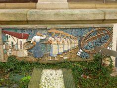 """""""LA SARDINERA"""". Mosaico rectangular en tesela cerámica modelado, en relieve,  por Paco Presa Merodio (Torrelavega, 1961 -). Instalado en 2007, fue realizado  en pasta de loza y arcilla roja y decorado con esmaltes y engobes coloreados, cocidos a 1050-1100º C. Rememora la popular figura de la sardinera reproduciendo: una vivienda de pescadores (entre txitxarra y portalada); una conocida postal de principios de siglo XX; un grupo de sardineras y una cesta con sardinas sobre una red de pesca."""