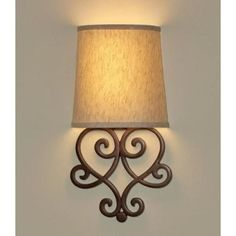 """Assembled Dimensions: 10"""" W x 19"""" H Helix Heart Scroll Wall Art Sconce with Tan Fleck Shade and Bronze Base  The Helix Heart Scroll Wall Art Sconce is a beautiful decorative lighting fixture that adds both elegance and ambiance to your home. Its ornate and detailed design complements classic and contemporary styles al Indoor Wall Sconces, Wall Sconce Lighting, Pendant Lighting, Chandelier, Battery Operated Wall Sconce, Bronze, Heart Wall, Hanging Pictures, Fabric Shades"""
