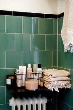 Det här badrummet i tjugotalsstil i brytpunkten mot funkis totalrenoverades i utsökt originalstil. Det inbyggda badkaret återanvändes på sin plats, den infällda tvålhyllan återanvändes och badrummet fick moderna tätskikt och vackert franskinspirerat grönt kakel med svart bård på väggarna och vitt sexkantigt klinker på golvet.