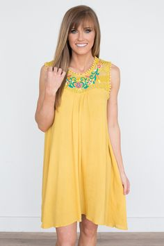 Shop our Floral Embroidered Dress in Mustard. Featuring a lace top detail and pompom trim along the arm holes. Free shipping on US orders!