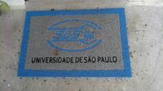 Tapete de porta com inscrição da Universidade de São Paulo.A identidade acima em azul claro provavelmete se trata de algum prestador de serviço da universidade.Destina-se às pessoas que eventualmente irão passar pela porta.