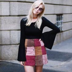 Look com saia de patchwork e blusa de manga comprida preta.