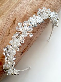 ETERNITY SWAROVSKI CRYSTAL HEADBAND  Wedding headpiece offers an elegant touch of radiant sparkle for your bridal look. This bridal headband features hand-wired rhinestones and Swarovski crystals in a swirling floral design. Pin loops are located on each end for added security and comfort.    MEASUREMENTS  Wedding headband measures approximately 1 inch wide. AVAILABLE FINISH  Bridal headpiece is available in Classic Silver. This timeless finish offers a bright silver hue with a lustrous…