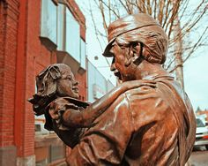 """*Worker greets daughter    1984 Larry Anderson's statue """"Coming Home"""" depicts a railway worker greeting his child. It's located in front of Heritage Bank on the corner of South 56th Street and South Tacoma Way. The statue was erected in honor of Tacoma's Centennial (1884-1984)"""