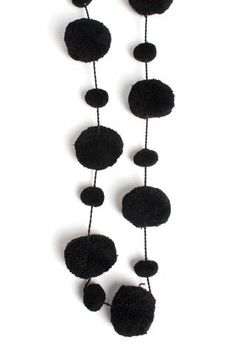 A bold string of 100% wool Pom Poms in black, a cool accessory for a contemporary home; kid's bedrooms, living spaces or Christmas decorations. 100% Wool. Handmade in India.