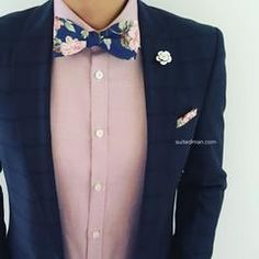 Men's fashion outfit. Navy blazer, pink button down, floral bow tie, pocket square, lapel pin.