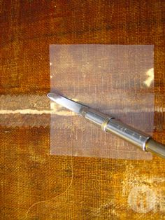 Unió de la meitat inferior de les dues teles que formen el quadre amb grapes de fil i reforç