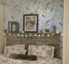 Super-king size headboard made out of pallet wood and old tester pots of paint