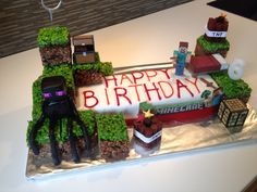 Minecraft crafty cake. Made with a pre bought Tesco cake. Homemade White and milk chocolate crispy blocks, with TNT from liquorice and Enderman from sugar paste fondant iceing. Much loved for my 6 year olds boys birthday.
