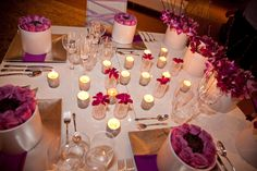 Party table decor with white, silver, and bright purple.
