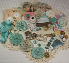 many vintage shades of aqua, pearl and taupe...yo yo's, buttons, snips of barkcloth, quilt, quilt block pieces, old black and white baby photo.....lots of sweet gatherings of aqua...