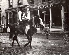 """Throwback Thursday! A """"cowgirl"""" on parade downtown Oshawa. The girl is dressed in a western costume, riding a pinto down Simcoe Street in parade, perhaps for a Wild West show or a circus parade. The buildings in the background, left to right, are the corner of Dominion Bank, Germond's Barber Shop and T.B. Mitchell's Drug Store.  """"Cow Girl"""" On Parade c.1910. Photograph from the Thomas Bouckley Collection Western Costumes, Wild West Show, Horse Riding, Fun Facts, Photograph, Museum, Cow Girl, Drug Store, Horses"""