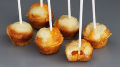 "Recipe with video instructions: Bite into these delicious ""cake pops"" to reveal a molten cheesy center! Ingredients: 6 tbsp pizza dough, 6 cubes cheddar cheese"