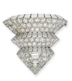 AN ART DECO DIAMOND BROOCH, BY SUZANNE BELPERRON   Designed as three graduated tiers of pavé-set diamonds with matt segmented bands between, to the baguette-cut diamond arrowhead terminal, circa 1935, 3.2 cm high, with French assay marks for platinum and gold  By Suzanne Belperron