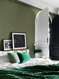 Scandinavian inspired bedroom with rich green colors and black accents