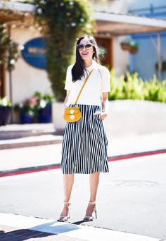 A polished white top is worn with a striped midi skirt, crossbody yellow bag, and ankle-strap sandals