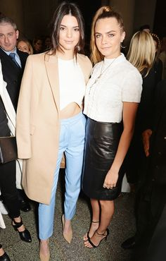 Kendall Jenner and Cara Delevingne at London Fashion Week. Kendall wearing a camel coat over a white crop-top. Cara wearing a leather pencil skirt.