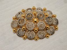 This vintage brooch is a very attractive combination of silver and gold tone metal. The silver tone metal is in a half dome wire mesh design. Then there are gold tone metal...