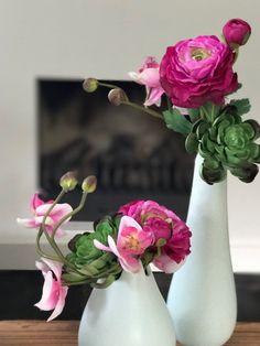 tafelstukje met zijden ranonkel, roze orchidee en kunstplantje. www.abonneefleur.nl