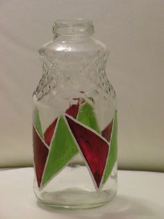 A SLICE OF MELON  •Upcycled bottle with geometric design in green and burgundy. •Hand painted •Materials: Glass bottle (32oz), Glass paint •Décor ideas: Pop a few flowers in to make this piece an elegant vase.