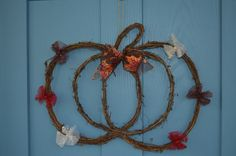 - Pumpkin shaped twig wreath wrapped with tulle bows and an autumn leaf wired…