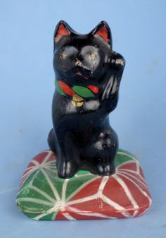 "Maneki Neko on a Pillow - Painted Clay. Circa Mid-20th Century. 4-1/2"". Underneath the Pillow is a Shunga (Erotic) Scene."