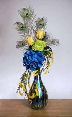 modern ostrich feather flower arrangement | Large contemporary floral arrangement with peacock feathers, yellow ...